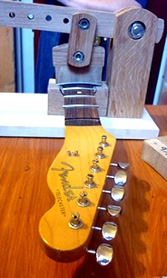 My home-made fret press in action, securing frets